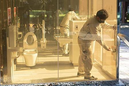 EinMann schließt die Tür einer neu installierten öffentlichen Toilette mit transparenten Wänden, die im Yoyogi Fukamachi Mini Park im Bezirk Shibuya steht. Die drei Toiletten aus transparentem Glas werden undurchsichtig, sobald jemand eintritt und die Tür verschließt. Foto: Rodrigo Reyes Marin/ZUMA Wire/dpa