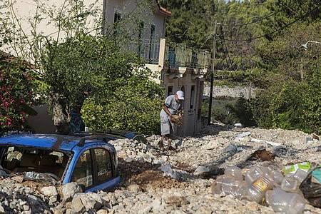 Ein Mann räumt Steine aus dem Weg. In zahlreichen Regionen Westgriechenlands und auf der Halbinsel Peloponnes fiel zudem der Strom aus. Foto: Nikiforos Stamenis/AP/dpa