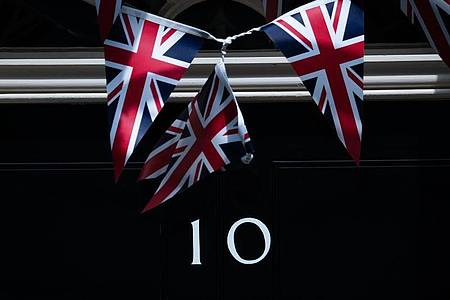 Fähnchen vor der Tür der 10 Downing Street. Aus Protest gegen das Verhalten des britischen Regierungsberaters Dominic Cummings in der Corona-Krise ist Staatssekretär Douglas Ross zurückgetreten. Foto: Aaron Chown/PA Wire/dpa