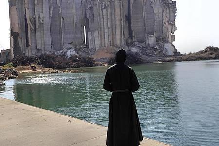 Ein Priester sieht im Hafen von Beirut auf die bei der Explosion vor einem Jahr zerstörten Getreidesilos. Viele Menschen verloren bei der Katastrophe ihr Leben. Foto: Hussein Malla/AP/dpa