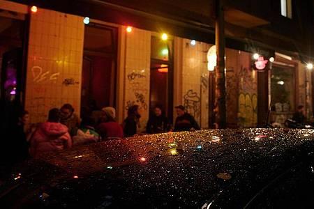 Kurz nach der Sperrstunde sind noch Gäste vor einer Bar in Neukölln. Foto: Annette Riedl/dpa