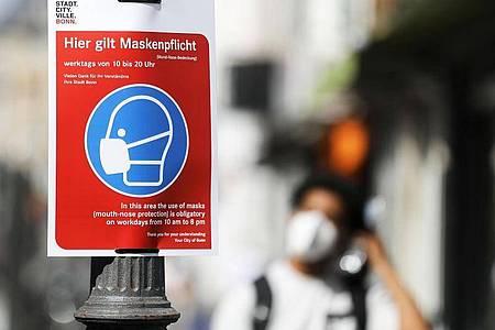 """Ein Schild mit der Aufschrift """"Hier gilt Maskenpflicht"""" hängt in der Fußgängerzone. Foto: Oliver Berg/dpa"""