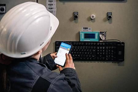 Auf der morgendlichen Routinerunde durchs Kraftwerk speichert die angehende Anlagenmechanikerin Lisa Maria Schippl die Betriebswerte einer Gasturbine in einer Smartphone-App. Foto: Zacharie Scheurer/dpa-tmn