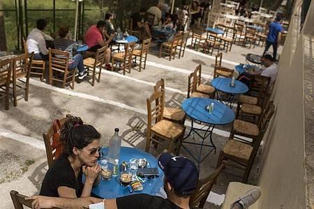 Gäste sitzen in einem Café im Stadtteil Monastiraki im Zentrum Athens. Foto: Socrates Baltagiannis/dpa