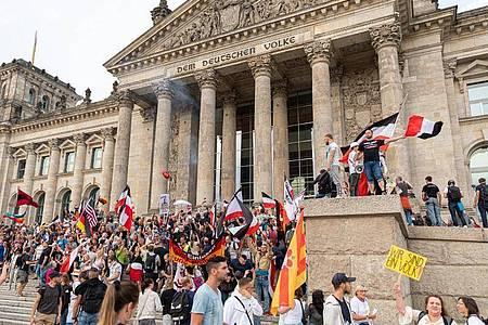 Teilnehmer einer Kundgebung gegen die Corona-Maßnahmen stehen auf den Stufen zum Reichstagsgebäude. Foto: Achille Abboud/NurPhoto/dpa