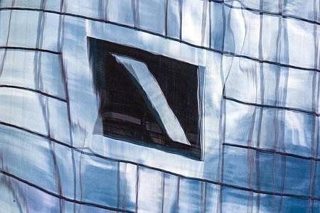Die Zentrale der Deutschen Bank in Frankfurt am Main spiegelt sich in einer Glasfassade. Foto: Boris Roessler/dpa