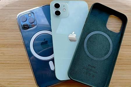 Apple bietet für das iPhone 12 (Mitte) und das iPhone 12 Pro (links) spezielle Schutzhüllen an, die mit dem neuen drahtlosen Ladesystem MagSafe funktionieren. Foto: Christoph Dernbach/dpa-tmn