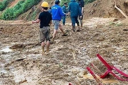Dorfbewohner waten durch Schlamm, nachdem ein Erdrutsch ein Dorf im ländlichen Bezirk Phuoc Loc in der Provinz Quang Nam überschwemmt hat. Foto: Lai Minh Dong/VNA/AP/dpa