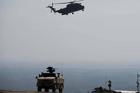 Ein Hubschrauber CH53 der Bundeswehr fliegt bei Masar-i-Scharif in Afghanistan über einen Dingo. Foto: picture alliance / dpa