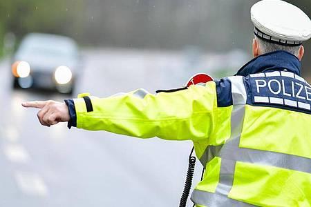 Ein Polizist während einer Geschwindigkeitskontrolle an einer Bundesstraße. Foto: Uwe Anspach/dpa/Symbolbild