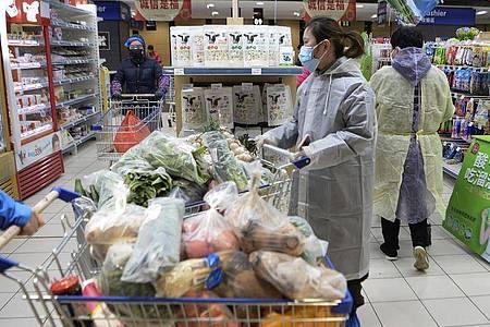 Kunden in einem Supermarkt beim Einkaufen. Foto: CHINATOPIX/AP/dpa/Symbolbild