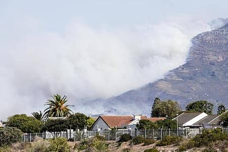 Weißer dichter Rauch steigt über dem Tafelberg auf. Foto: Lyu Tianran/XinHua/dpa