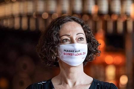 Maske trägt längst nicht jeder. Mit Sprüchen auf Plakaten, Bierdeckeln und Masken sollen Gäste in Berlin an die Corona-Schutzmaßnahmen erinnert werden. Foto: Bernd von Jutrczenka/dpa