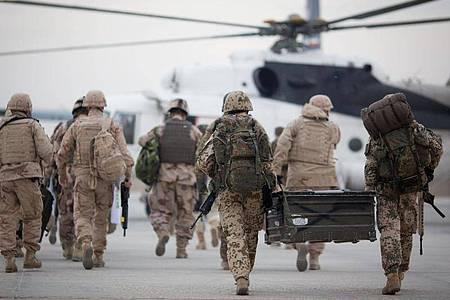 Bundeswehrsoldaten (r) auf dem Weg zu einem zivilen Hubschrauber. Die Nato will nach der Unterzeichnung eines USA-Taliban-Abkommens über Wege zum Frieden in Afghanistan ein Viertel ihrer Truppen aus dem Land abziehen. Foto: Kay Nietfeld/dpa