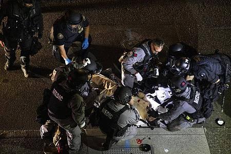 Ein angeschossener Mann wird inPortland von Sanitätern behandelt. Der mutmaßliche Schütze ist offenbar von der Polizei getötet worden. Foto: Paula Bronstein/FR171772 AP/dpa