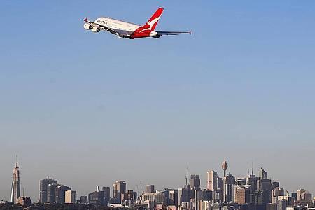 Eine Maschine der australischen Fluggesellschaft Qantas fliegt über Sydney. Foto: Bai Xuefei/Xinhua/dpa