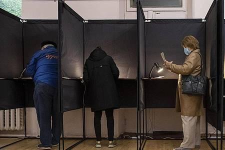 Bürger geben in einem Wahllokal in Vilnius ihre Stimme ab. Foto: Mindaugas Kulbis/AP/dpa