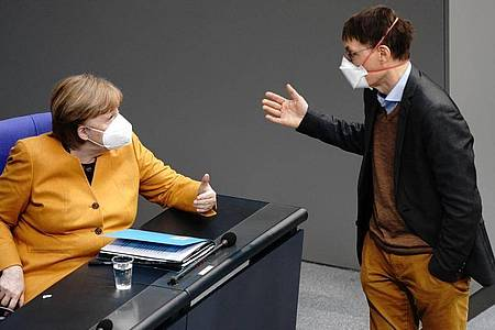 Bundeskanzlerin Angela Merkel (CDU) diskutiert mit SPD-Gesundheitsexperte Karl Lauterbach. Foto: Kay Nietfeld/dpa