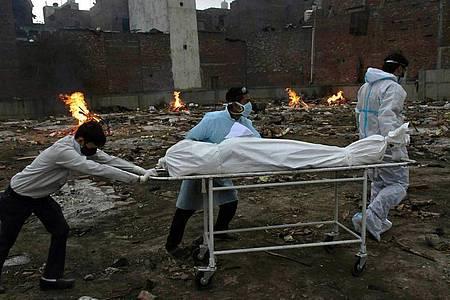 Der Leichnam eines Corona-Patienten wird auf einer Trage in einem Krematorium zur Einäscherung geschoben. Foto: Ishant Chauhan/AP/dpa