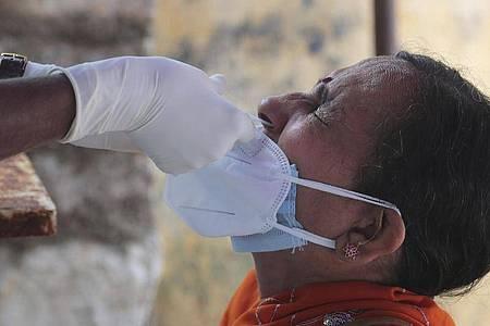 Ein medizinischer Mitarbeiterin der indischen Stadt Hyderabad entnimmt einer Frau einen Nasenabstrich für einen Corona-Test. Foto: Mahesh Kumar A/AP/dpa