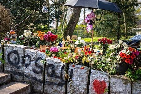 Blumen erinnern im Wollepark in Delmenhorst an einen verstorbenen 19-Jährigen. Für die Familie sind die Umstände seines Todes nach einem Polizeieinsatz aufklärungsbedürftig. Foto: Sina Schuldt/dpa