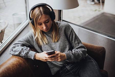 junge Frau hört Podcast