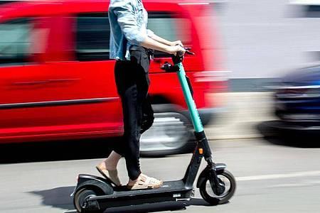 Eine junge Frau unterwegs mit einem E-Scooter in Hannover. Foto: Hauke-Christian Dittrich/dpa