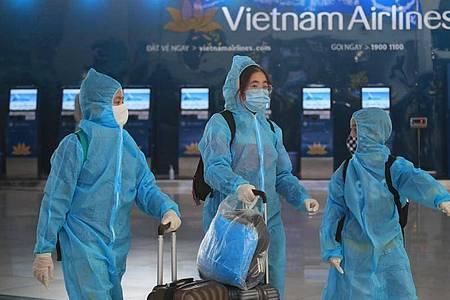 Passagiere in voller Schutzkleidung gegen das Coronavirus gehen durch den Flughafen Hanoi. Foto: Hau Dinh/AP/dpa