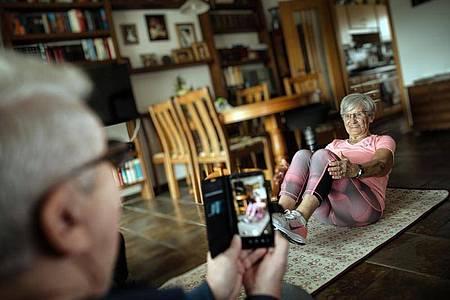 Turn-Internetstar Erika Rischko wird von ihrem Mann Dieter für ihre Social-Media-Auftritte in ihrem Wohnzimmer gefilmt. Foto: Ralph Matzerath/dpa