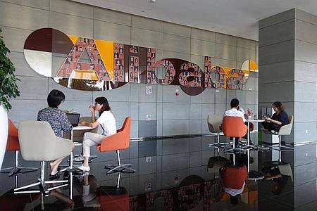 Mitarbeiter sitzen in einem Foyer der Firmenzentrale von Alibaba in Hangzhou. Foto: Andre Klohn/dpa