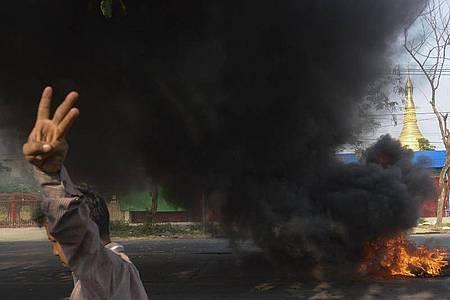 Ein Demonstrant zeigt den Dreifingergruß als Zeichen des Widerstands vor brennenden Reifen in Yangon. Foto: Uncredited/AP/dpa