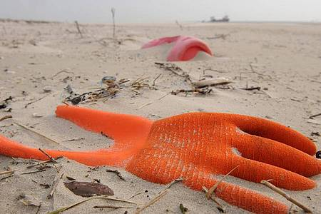 Angespülter Unrat in Form eines Arbeitshandschuhs und eines Kunststoffkanisters am Strand der Vogelschutzinsel Memmert, Niedersachsen. Foto: picture alliance / dpa