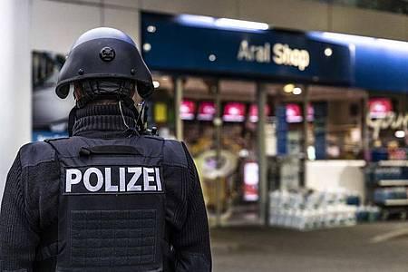 Ein Polizist steht vor der Tankstelle, an der ein Angestellter von einem Mann erschossen worden ist. Foto: Christian Schulz/Foto Hosser/dpa