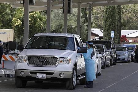 Mitarbeiter des Gesundheitswesens nehmen in einem Covid-19-Testzentrum im US-Bundesstaat Kalifornien Proben von Personen. Foto: Ben Margot/AP/dpa