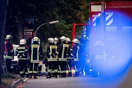 Feuerwehrleute stehen auf der gesperrten Volksgartenstraße in Dortmund beim Einsatz im Zusammenhang mit der Wohnungsdurchsuchung. Foto: Fabian Strauch/dpa