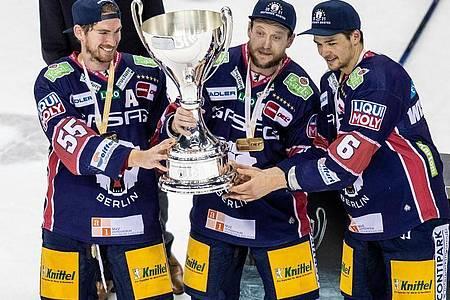 Die Berliner John Ramage, Frank Hördler und Kai Wissmann (l-r) mit dem Meisterpokal. Foto: Andreas Gora/dpa