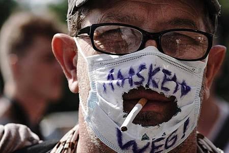 """""""Masken Weg!"""" steht auf dem """"Mundschutz"""" eines Teilnehmers einer Demonstration gegen die Corona-Maßnahmen. Künftig wird es zur Pflicht auf Demonstrationen in Berlin Masken zu tragen. Foto: Michael Kappeler/dpa"""