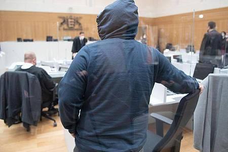 """Ein Prozessteilnehmer mit einer Kapuze kommt kurz vor Beginn des Prozesses gegen die rechtsterroristische Vereinigung """"Gruppe S."""" im Oberlandesgericht Stuttgart-Stammheim. Foto: -/dpa-pool/dpa"""