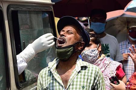 Ein Mitarbeiter des Gesundheitswesens entnimmt in Kalkutta aus einem Auto heraus einen Abstrich für einen Corona-Test. Foto: Sumit Sanyal/SOPA Images via ZUMA Wire/dpa