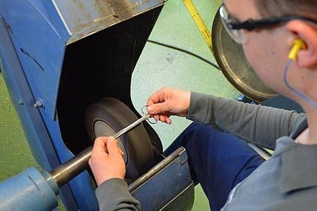 Frischer Schliff: Instrumente, die der angehende Chirurgiemechaniker Pascal Scheu bearbeitet, landen später zum Beispiel in den Händen von Ärztinnen und Ärzten. Foto: B. Braun Melsungen AG/dpa-tmn