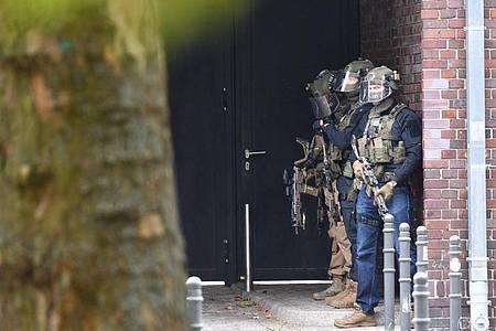 Bewaffnete Einsatzkräfte der Polizei vor dem Schulgebäude. Foto: Paul Zinken/dpa-Zentralbild/dpa
