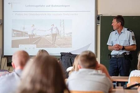 Bundespolizist Manfred Ludwig klärt Kinder der Klassen 5 und 8 über Gefahren im Bahnumfeld auf, unter anderem über die Gefahren von Fotos im Bahngleis. Foto:Nicolas Armer