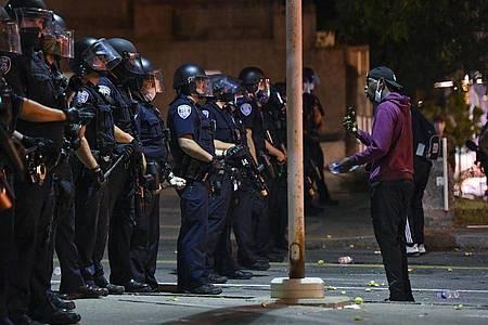 Ein Demonstrant steht während einer Demonstration vor Polizisten in Rochester. Nachdem ein 41-jähriger Afroamerikaner infolge eines brutalen Polizeieinsatzes verstarb, wurden sieben Beamte vom Dienst suspendiert. Foto: Adrian Kraus/AP/dpa
