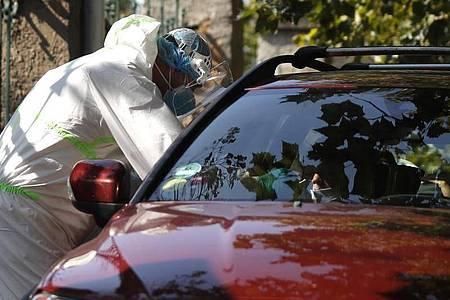 Prag:Ein junger Autofahrer wird an einer Drive-in-Teststation auf Covid-19-Symptome geprüft. In Tschechien breitet sich das Coronavirus weiter rasant aus. Foto: Petr David Josek/AP/dpa