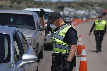 Polizisten kontrollieren im US-Bundesstaat New Mexico, ob nicht mehr als zwei Personen in den vorbeifahrenden Autos sitzen. Foto: Morgan Lee/AP/dpa