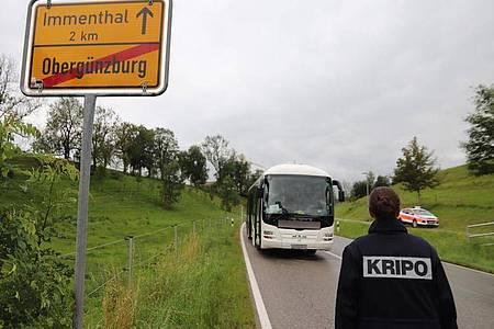 Eine Mitarbeiterin der Kripo geht auf den am Straßenrand stehenden Linienbus zu. Foto: Benjamin Liss/dpa