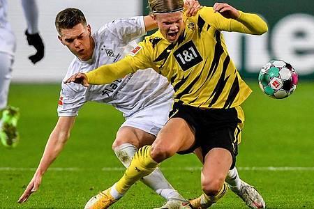 Mönchengladbachs Matthias Ginter (l) in Aktion gegen Dortmunds Erling Haaland. Foto: Martin Meissner/Pool AP/dpa