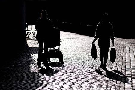 Zwei Frauen gehen im Gegenlicht durch eine Straße in der Innenstadt vonOldenburg. Foto: Hauke-Christian Dittrich/dpa