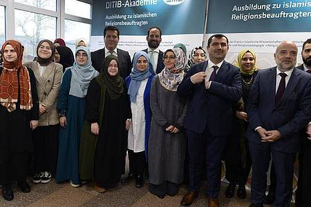 Kazim Türkmen (2.v.r), Vorsitzender Ditib Bundesvorstand, und Markus Kerber (r.), Staatssekretär im Bundesinnenministerium, mit ersten Teilnehmern der Imam-Ausbildung. Foto: Roberto Pfeil/dpa