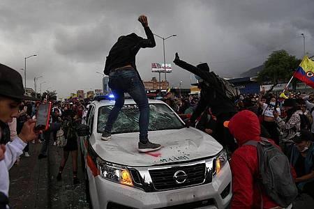 Demonstranten schlagen auf einen Polizeiwagen während des Protests in Bogota. Foto: Camila Diaz/colprensa/dpa